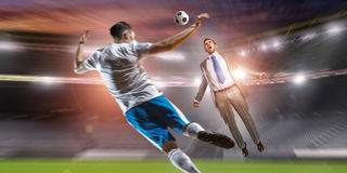Businessman and player fighting for ball . Mixed media Stock Photos
