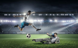 Businessman and player fighting for ball Stock Photo