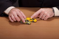 Businessman playing. With his dream cars Royalty Free Stock Photos