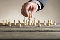 Businessman playing chess moving white king piece Stock Image