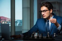 The businessman playing chess in strategy concept. Businessman playing chess in strategy concept Royalty Free Stock Images