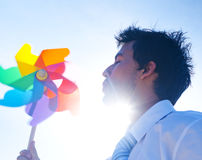 Businessman Playing with a Colorful Pinwheel Stock Images