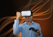 Businessman playing with computer game controller with virtual reality headset with curvy lines back Stock Images