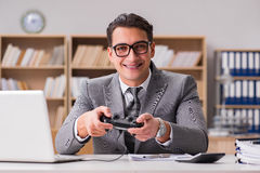 The businessman playing computer games at work office Stock Image