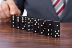 Businessman playing domino on desk Stock Photo