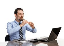 Businessman playing on flute in front of laptop - isolated on white background Stock Photography