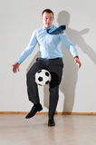 Businessman is playing football Stock Images