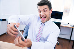 Businessman playing in game on the phone in office Stock Image
