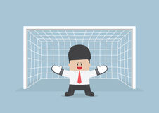 Businessman playing goalkeeper standing in front of goal ready t Stock Image