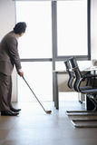 Businessman playing golf in his office, holding golf club Stock Photo