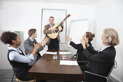 Businessman playing guitar in business meeting stock images