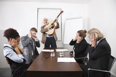 Businessman playing guitar in business meeting Royalty Free Stock Photos