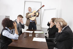 Businessman playing guitar in business meeting stock image
