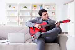 The businessman playing guitar at home Royalty Free Stock Photos