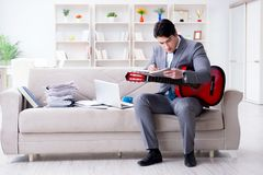The businessman playing guitar at home Royalty Free Stock Images