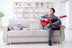 The businessman playing guitar at home Royalty Free Stock Image
