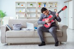 The businessman playing guitar at home Stock Image