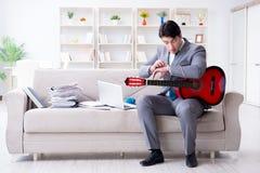 The businessman playing guitar at home Stock Photos