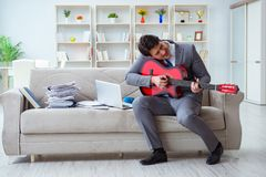 The businessman playing guitar at home Royalty Free Stock Photo