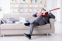 The businessman playing guitar at home Stock Images