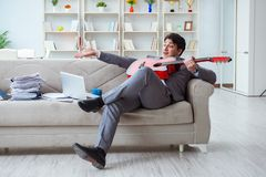 The businessman playing guitar at home Royalty Free Stock Photography