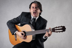 Businessman playing the guitar Stock Photography