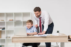 Businessman playing on laptop with his son. At office Stock Photo
