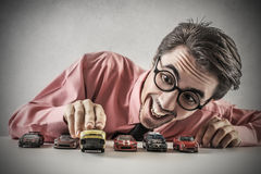 Businessman playing with little cars Royalty Free Stock Photo