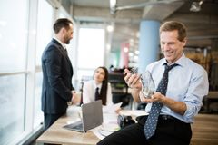 A businessman is playing with a metal toy slinky. Office workers are speaking in the office behind. A businessman is playing with a metal toy slinky. He is stock photography