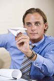 Businessman playing with paper airplane Royalty Free Stock Photos