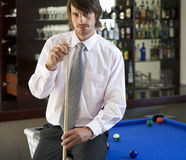 A businessman playing pool in a bar Stock Image