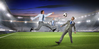 Businessman playing soccer . Mixed media Royalty Free Stock Image