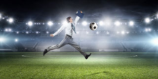 Businessman playing soccer . Mixed media Royalty Free Stock Photo