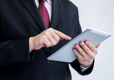 Businessman playing tablet- Hand Focused Royalty Free Stock Image