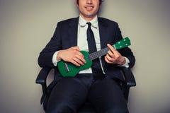 Businessman playing ukulele Royalty Free Stock Photography