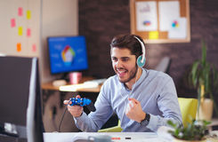 Businessman playing videogames in his office Royalty Free Stock Photo