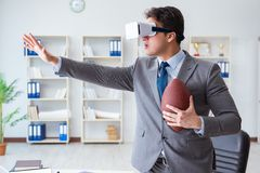 Businessman playing virtual reality football in office with VR g Royalty Free Stock Image