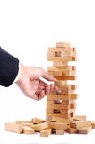 Businessman playing with the wood game (jenga). on white backgro Stock Images