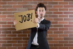 Businessman pleads with sign. Young businessman standing pleading with sign Need Job Royalty Free Stock Photo