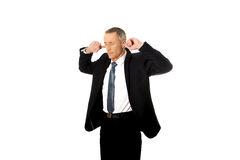 Businessman plugging his ears Royalty Free Stock Images