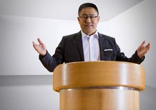 Businessman on podium speaking at conference with minimal background. Digital composite of Businessman on podium speaking at conference with minimal background Royalty Free Stock Image