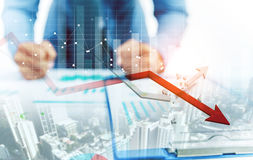 Businessman point at decreasing graph and increasing broken graph. With city background Stock Photos