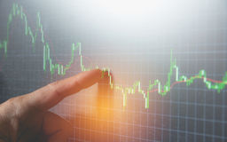 Businessman point finger at indicator graph and volume. Bar for analysis stock market on monitor background. business finance concept Stock Photography