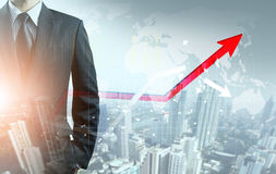 Businessman point at increasing graph and decreasing broken graph. With city background Royalty Free Stock Images