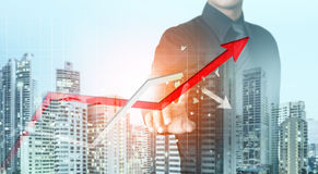 Businessman point at increasing graph and decreasing broken graph. With city background Royalty Free Stock Photos