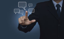 Businessman point to social chat sign and speech bubbles on blue Royalty Free Stock Photography
