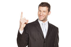 Businessman pointing. Young Businessman showing something by his index finger, isolated on white. You can add extra white space with your message to the bottom royalty free stock image
