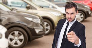Businessman pointing against car in showroom Stock Image