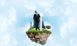 Businessman and pointing banner. Confident and successful businessman in black suit pointing upside with huge white arrow in his hands while standing on flying Royalty Free Stock Images