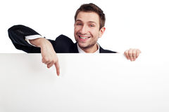 Businessman pointing at billboard. Portrait of young businessman pointing at blank white sign Stock Image